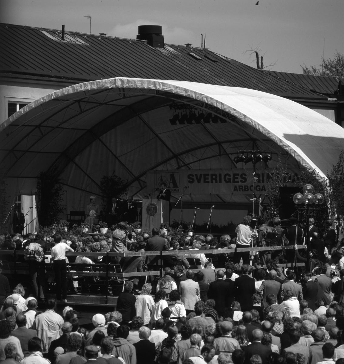 Statsminister Olof Palme talar på 550-årsjubileet av Sveriges första riksdag. På scenen sitter drottning Silvia, kung Carl XVl Gustaf, talman Ingemund Bengtsson och Bertil Karlsson (skymd). Journalisterna filmar och fotograferar. Allmänheten trängs på Stora torget. Scenen är uppförd på rådhusets innegård. Ovanför scenen är en tältkupol monterad. Riksdagsjubileet 1985
