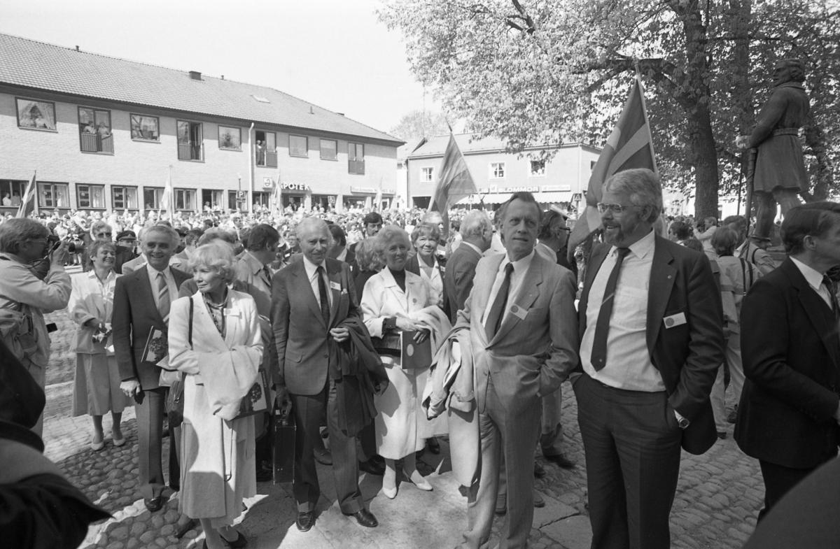 Riksdagsjubileet. I Arboga firas 550-årsminnet av Sveriges första riksdag. Politiker, så väl lokala som på riksplanet, är på väg in i Heliga Trefaldighetskyrkan. Den tidigare moderatledaren, Gösta Bohman, tillsammans med hustrun Gunnel, ses mitt i bild. Den skrattande kvinnan längst till vänster, kan vara Beatrice Ask, förbundsordförande i Moderata ungdomsförbundet. Fotografen, till vänster i bild, kan vara Conny Silén på Bärgslagsbladet. I bakgrunden ses Apoteket och Bellis Blommor. Allmänheten hålls på behörigt avstånd, på andra sidan Järntorget. Flaggorna vajar.