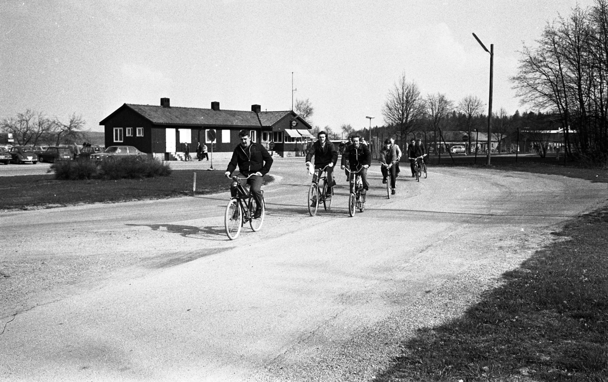 Arbetsdagen är slut, på CVA, Centrala Verkstaden. Männen cyklar hem. Person nummer två, från vänster, är Lars Englund. I bakgrunden ses bilparkeringen, byggnaden där vakten sitter och grinden som alla måste passera.