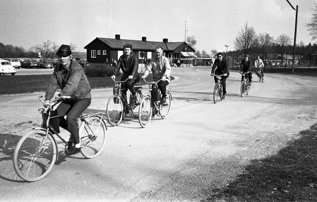 Arbetsdagen är slut, på CVA, Centrala Verkstaden Arboga. Männen cyklar hem med sina matväskor på styret. Nummer två, från vänster, är Yngve Nilsson och nummer fyra är Henry Fredriksson. I bakgrunden ses bilparkeringen, byggnaden där vakten sitter och grindarna som alla måste passera.