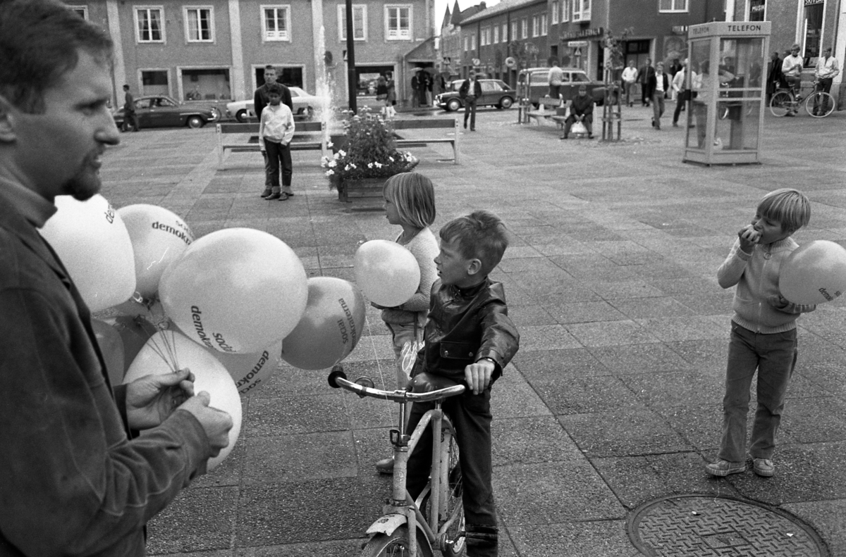 Socialdemokraterna har valmöte på Nytorget. Per-Olov Nilsson delar ut ballonger. På torget ses fontänen och en telefonkiosk. Människor rör sig över torget. Barn med cyklar. Bilar åker på Nygatan.