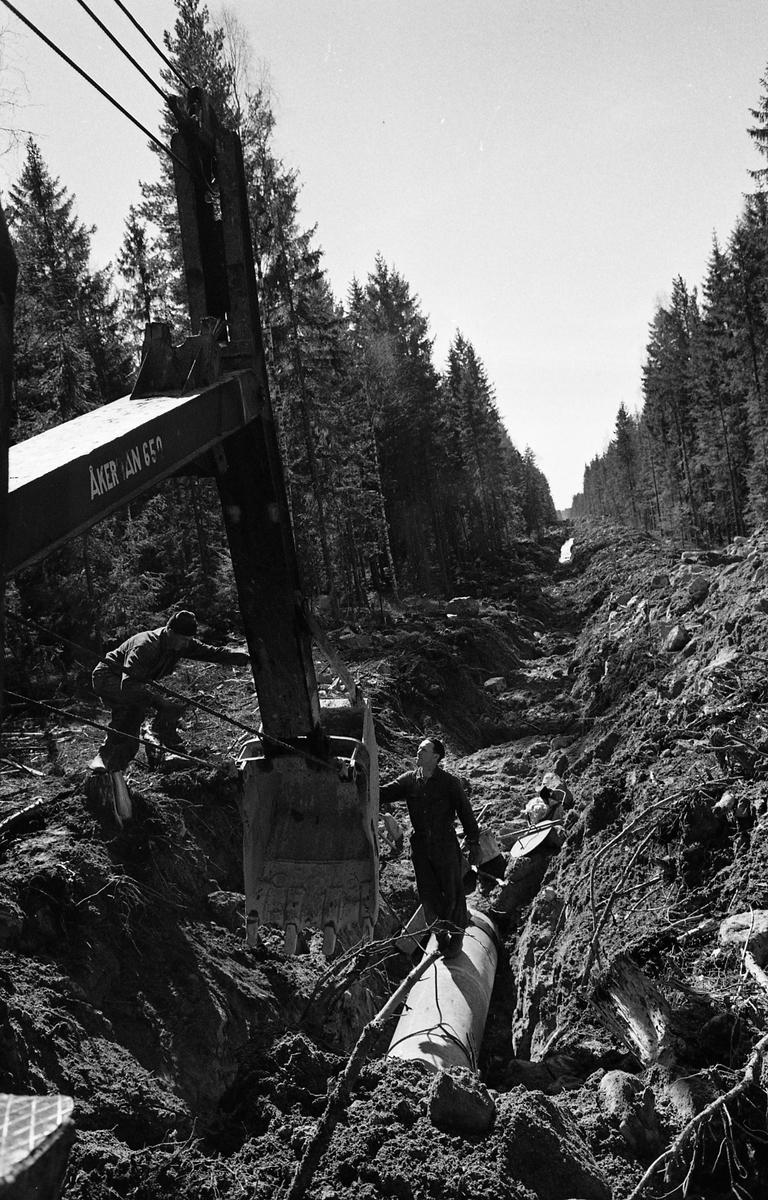 """Vattenverket byggs. Två man och en grävskopa arbetar med rörläggning i en """"gata"""" i skogen."""