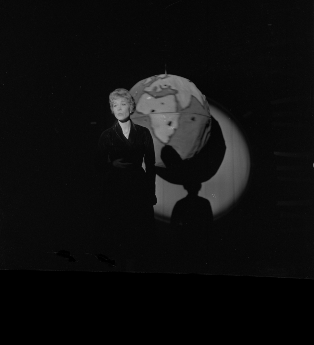 Lokalrevyn 1959 En ensam kvinna på scenen, en jordglob i bakgrunden.