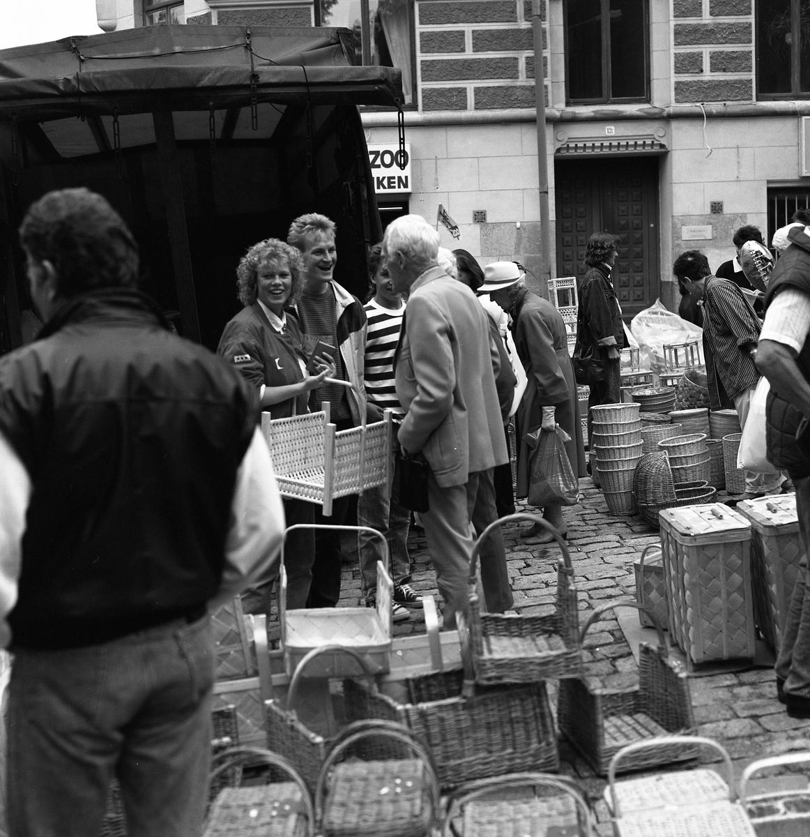 """Höstmarknad på Järntorget. Människor besöker torgståndet med korgar. En ung kvinna har en korg på armen och en plånbok i handen. Byggnaden i bakgrunden är """"Gamla Sparbankshuset"""" med ZOO-butiken i hörnet ner mot Arbogaån."""