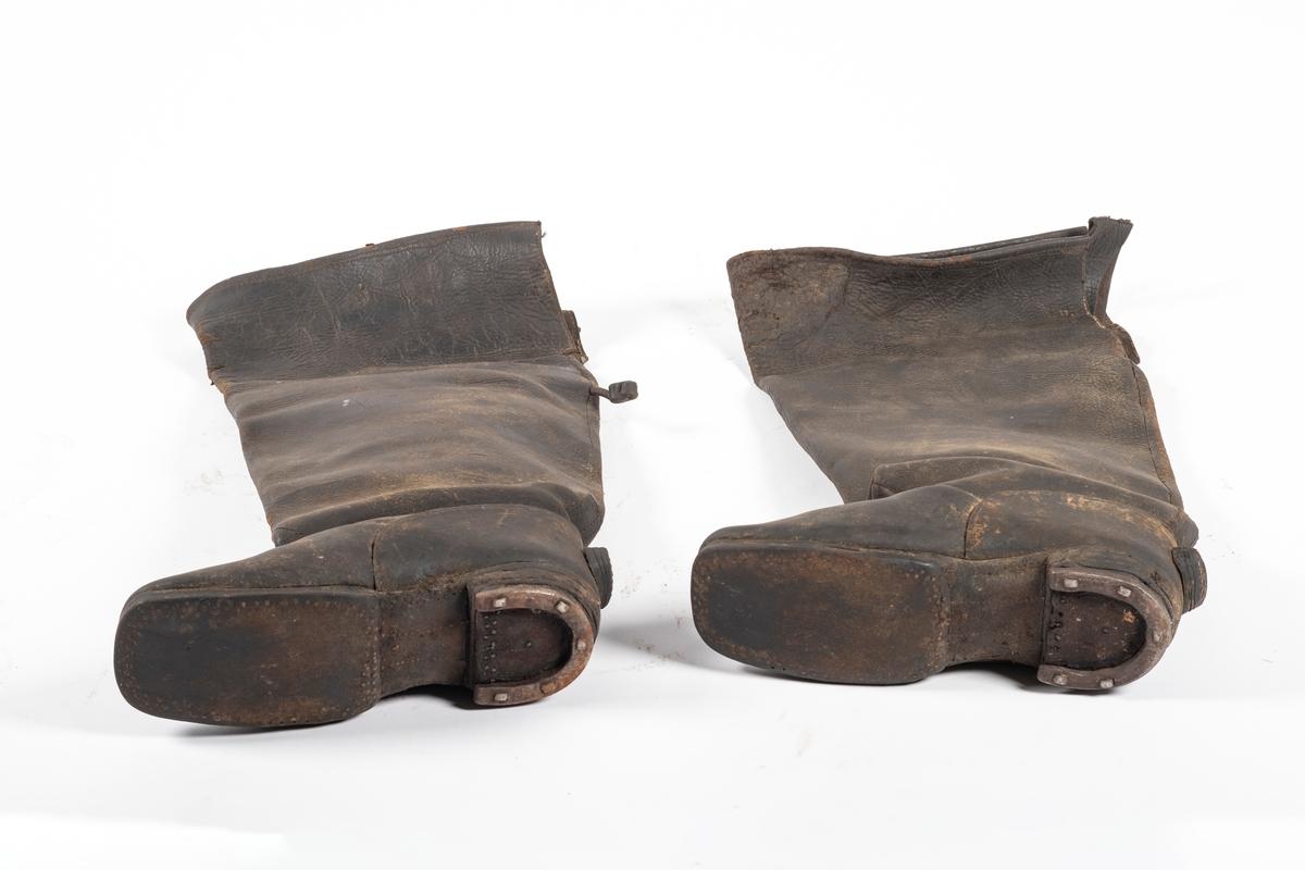 Støvelen er høy og blir videre mot toppen. Skotuppen er rett og skrår oppover. Bak på hælen er det sydd/spikret på en trekantet lærbit som står ut. Under hælen er det naglet på en halvsirkel av metall, lik en liten hestesko. Det er et snitt bak på støvelhalsen. Opp fra støvelens innside stikker det to brede lærremmer, muligens til å trekke på seg støvlene med. Materialet er mykt og kraftig. Bak på den ene støvelen henger en lærdusk