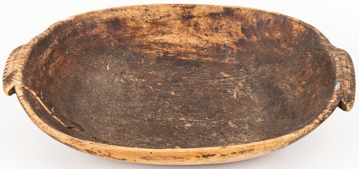 Träskål av björk, ovalt , försedd med öron med enkel punktornering. Omålat.