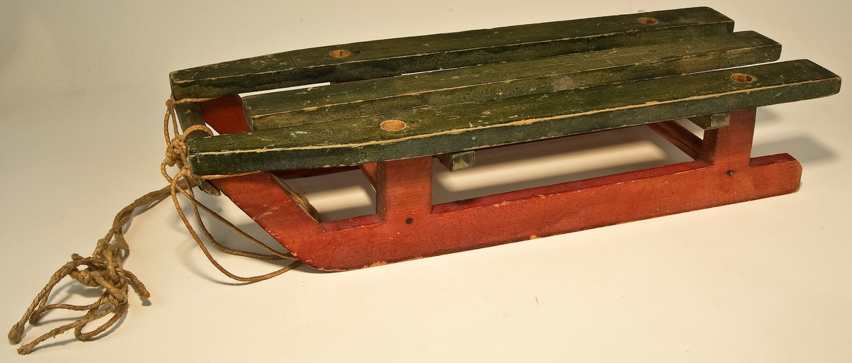 Kat: kort: Kälke av trä. Grön med röda medar. Tre bankar varav de yttre med hål för stakar (saknas.) Dragsnöre fästat framtill på tre punkter.  Tillhör leksakssamlingen från Tolvfors. För närmare uppgifter om tidigare ägare samt, åtkomst, se GM 24520  L: 310 mm  B: 118 mm  H: 68 mm  Neg.nr: A 92-901