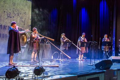 Bronsealderkledd band spiller på lur og andre blåseinstrumenter i blålig konsertbelysning på en scene.