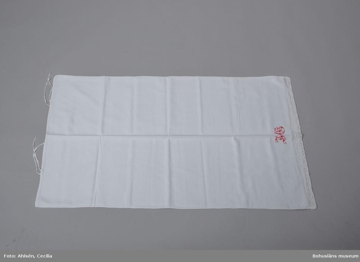 Långörngott av vit handvävd bomullslärft i kypert, vådbredd 65 cm. Sydd (maskinsydd) som en avlång påse med öppning i ena kortsidan med två par bomullsband för ihopknytning och en infälld spets i den andra. Mitt inunder spetsen märkt med J G  i plattsöm med rött bomullsgarn. Den 7 cm breda spetsen är virkad eller en kombination av flätat och snott i vitt bomullsgarn. Partiet är sedan dubbelvikt och fastsydd vid örngottets stadkant.