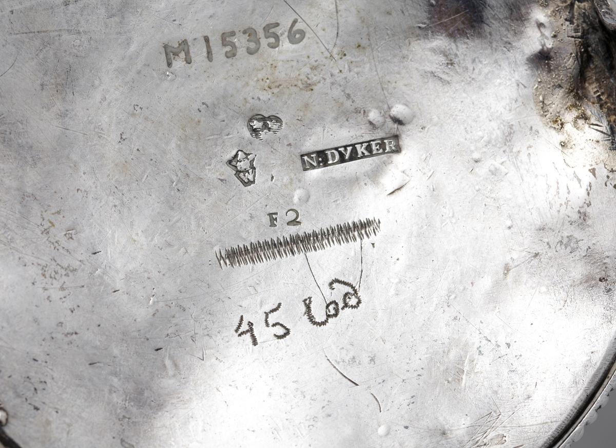 Kaffekanna i silver.  Cylindrisk modell på fyra tassfötter. Pärlstavsdekor upptill och nedtill, innanför denna en ciselerad palmettbård. Välvt lock med graverad bård och knopp i form av blombukett. Kort, rakt utstående holk för skaftet. Vid holkens mynning dekor av pärlbård, vid dess inre kortsida omgiven av en pålödd och ciselerad blomma. Försedd med svarvat, svärtat trähandtag, fäst med ett bladformat böjt silverstift (saknas). Stämplar på undersidan av kannan.