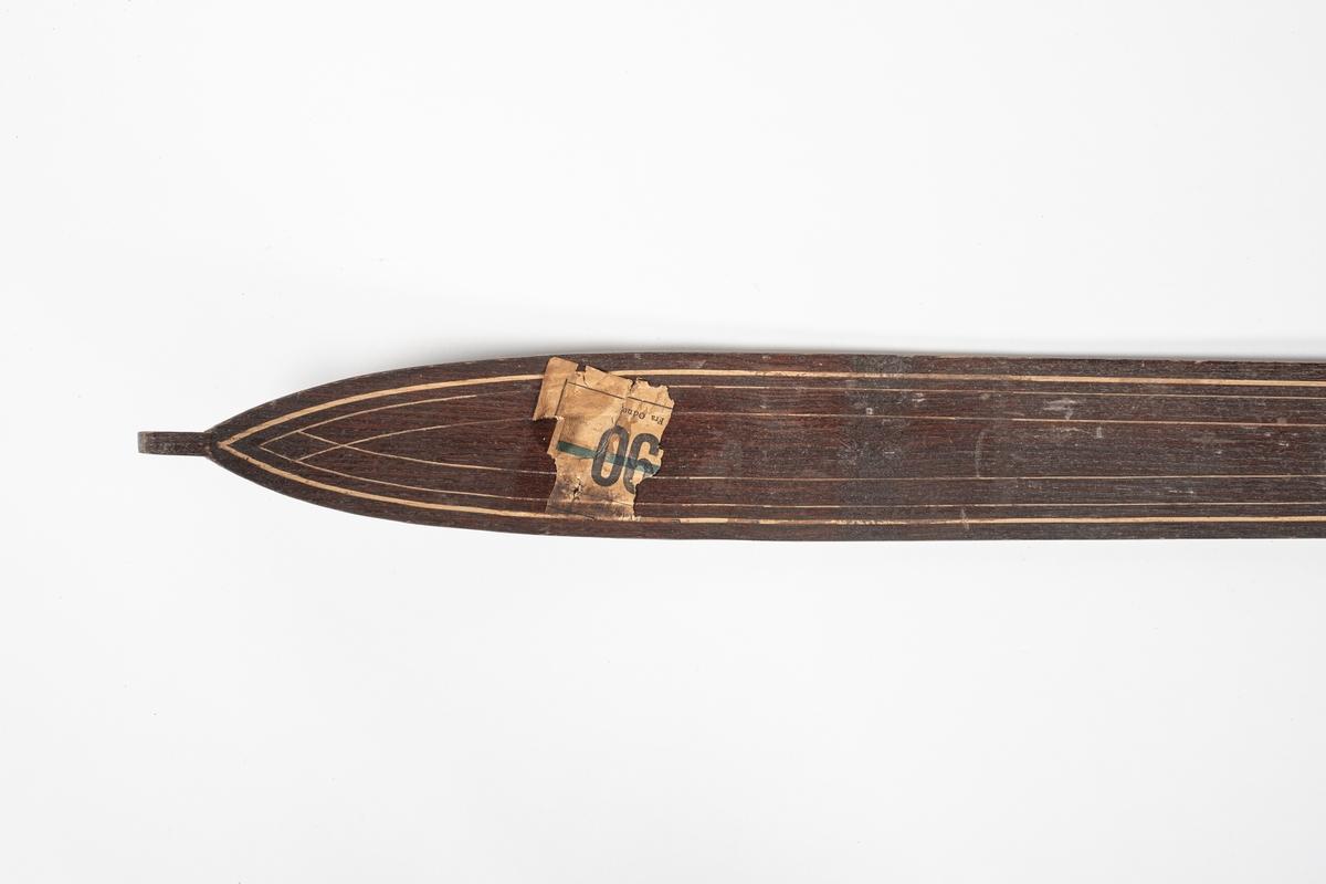 Ski med jevn bredde, svinger litt inn på midten. På midten av skien er det en forhøyning med påspikret plate som forsterkning. Bindingen består av lærremmer over tær og vrist, og bak hælen. Remmene er festet til en bøyd jernplate, som er festet i en spalte i skien, under forsterkningen. Skien er rett bak og spiss foran. Skien krummer oppover foran, og har en liten tapp ytterst. Under skien er det en renne i midten. Det er utskåret striper langs oversiden av skien som dekorasjon.