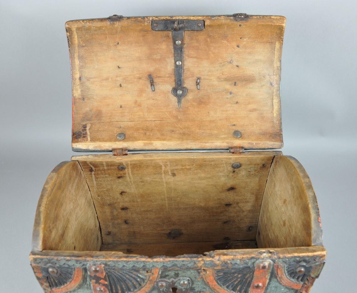 Skrin av tre, med hengslet lokk. Skrinet har rektangulær form med buet lokk, slik også fram- og bakside på skrinet er. På flatene er det skårene karveskurdroser i hjørnene og en åttebladet rosett i midten. Langs kantene siksakbord. På lokket er det et hengslet håndtak. På hjørnene av korpus er det klinket inn beslag av jern. Korpus har blå grunnfarge med rød dekormaling. Låsemekanisme mangler.