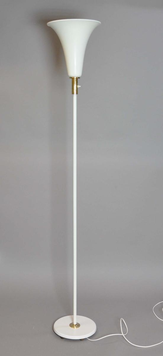 Stålampe av metall. Består av en rund sokkel med rettvinklet stang på midten. Øverst er det en lampeskjerm med oppovergående kjegleform med utoverbøyd rand. Midtpartiet av sokkelen og øverste del av stangen ved lysbryteren er belagt med messing.