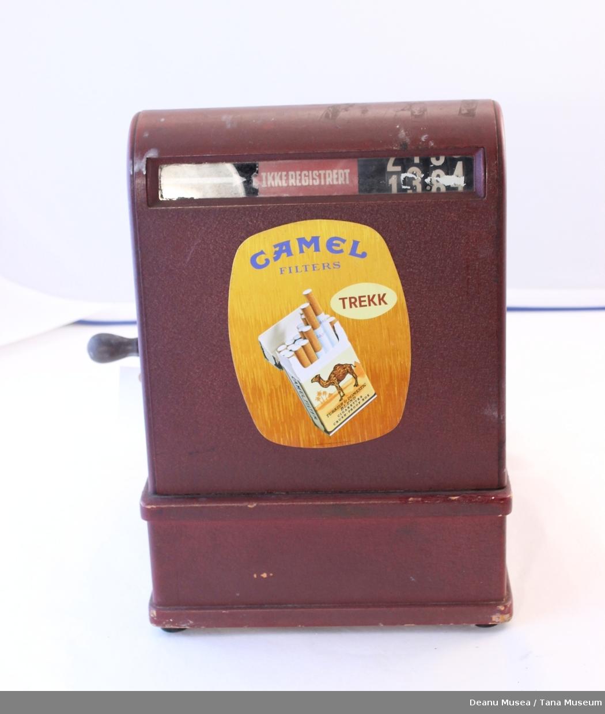 Rød kassaapparat. Camel sigarett reklame klistrert på apparatet.