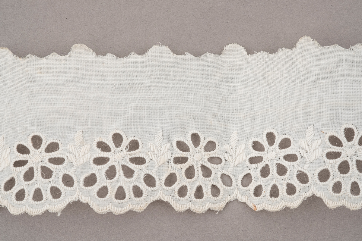 Hvit tekstilbånd med hullbroderinger av blomster langs den ene kanten. Den andre kanten er klipt opp i bølger. Endene er rettklipt.