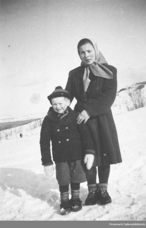 En kvinne og et barn fotografert ute, stående i en snødekt skråning. De er Reidar Mathisen og Bigga Mathisen.