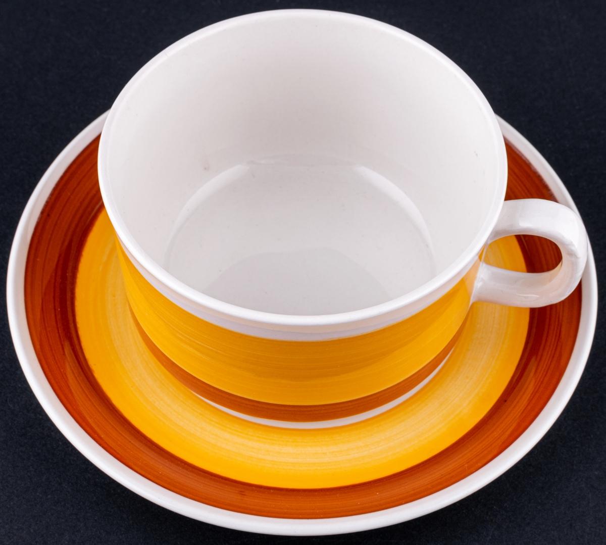 Kaffekopp med fat, i modellen BD och med dekoren Stina i vitglasyr med band i gult och brunt.