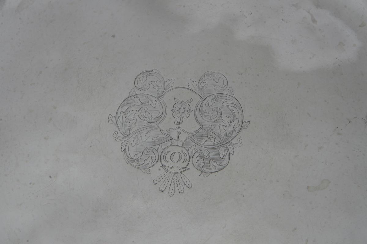 Sølv? Bånd- og bladornamenter langs kanten. Siselert våpenskjold med rose sentralt plassert. Jvnf. AS.310621. Stemplet på undersiden.