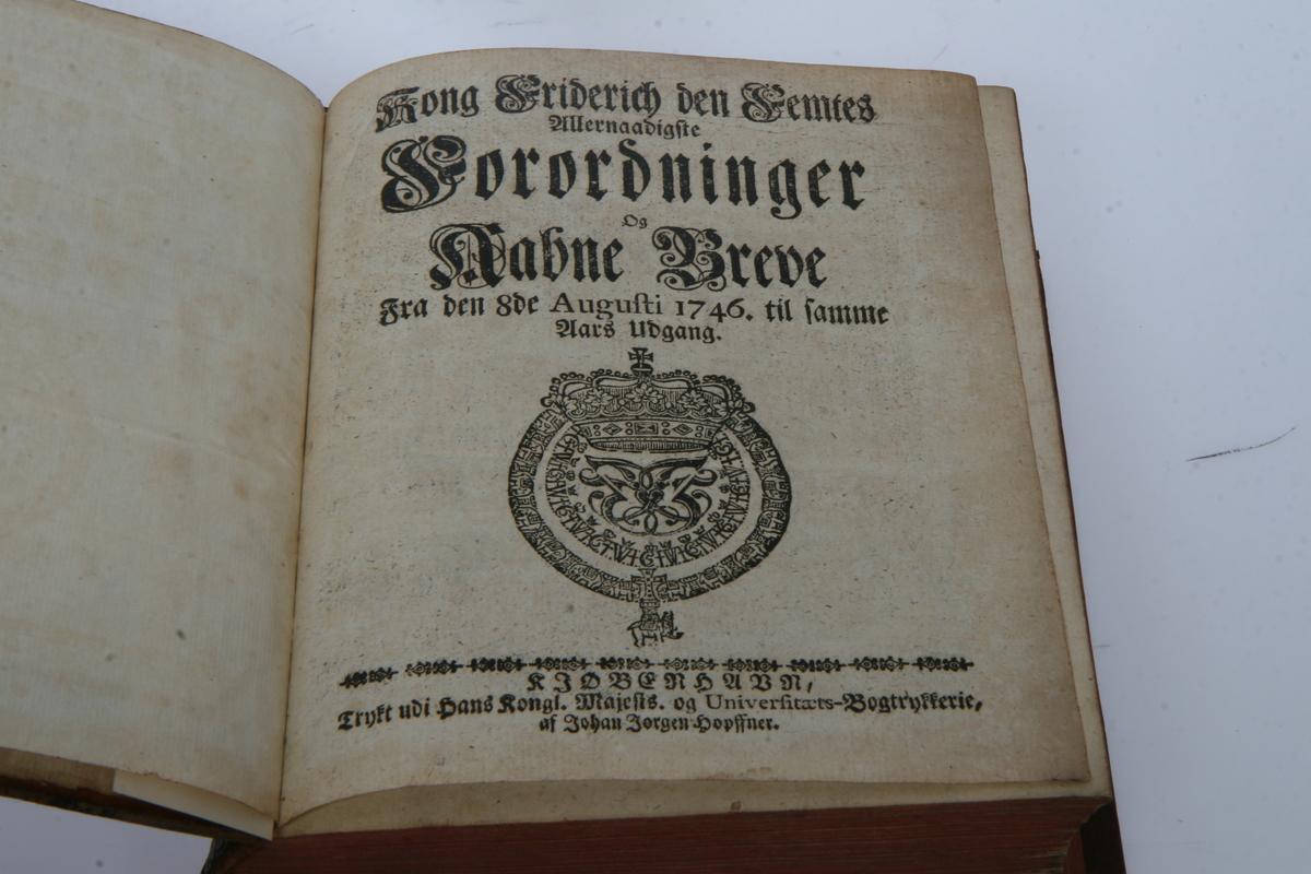 """Innbundet i skinn med gulltrykk og pressede ornamenter. """"Kong Friderich den Femtes allernaadigste Forordninger og Aabne Breve"""" 1746-1751. København u.å."""