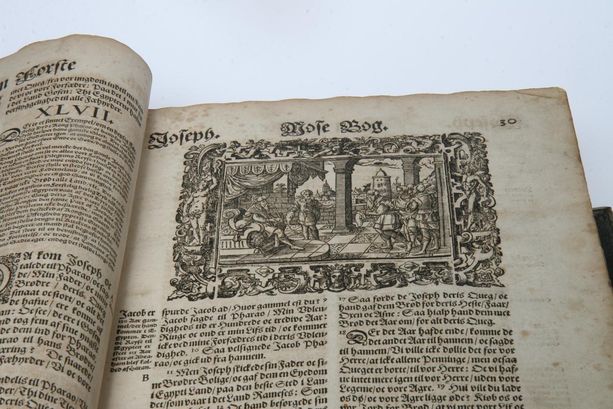 Christian IV's bibel. Skinnbind med pressete, forgylte ornamenter, messingbeslag i alle hjørner, to spenner. Den ene spennen er defekt. Skinnet restaurert, nye smussblad. Fem kobberstikk innklebet på permens innside.