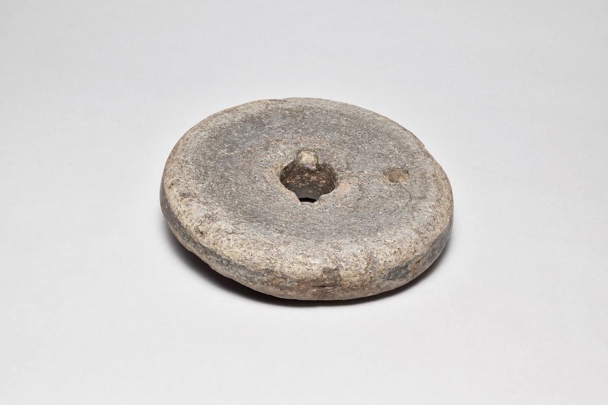 Snuskvarn av sten, rund, i två delar. Överliggaren med två hål, det ena för draghandtag. Underliggaren med ett hål.