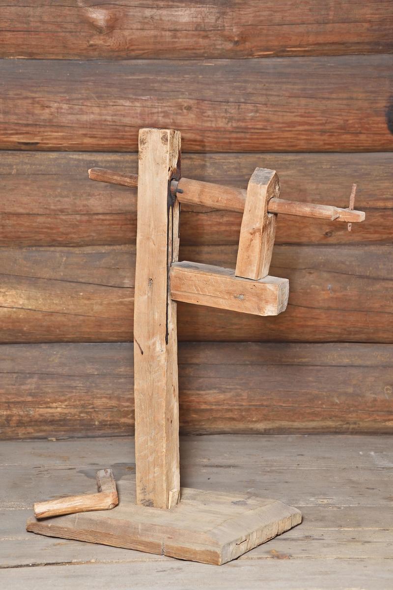 Snomaskin, repslagarredskap av trä. Rektangulär fotplatta med fasade kanter, fyrkantig ståndare med stöd för vevstången, vev med L-format handtag (avbrutet), i änden 2 spikar (att fästa repänden i).