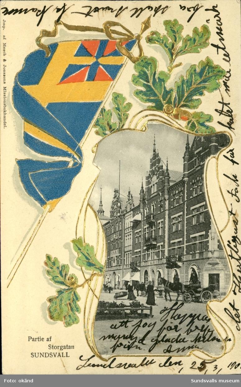 Vykort med bild över parti av Storgatan, det vänstra övre hörnet har utsmyckats med unionsflaggan.