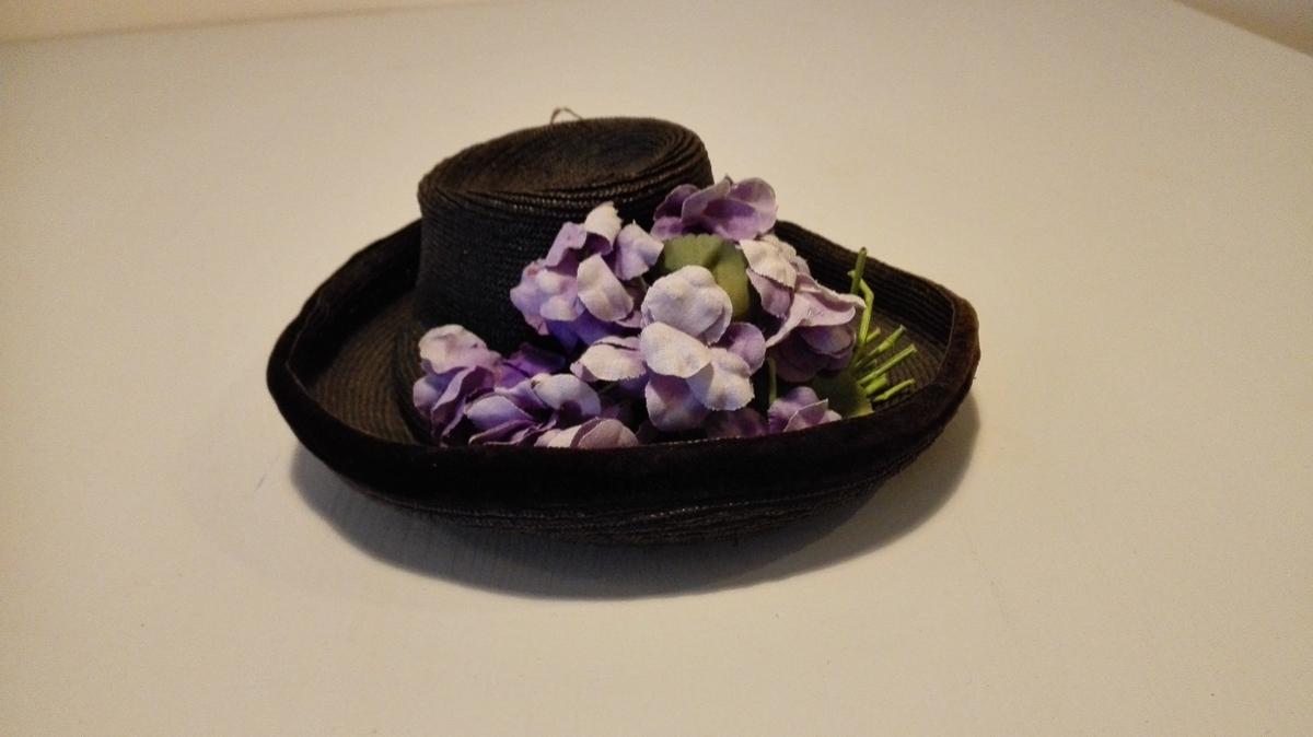 """Stråhatt til dame  Fletta og sydd saman av svartfarga tynne strå, kanta med fløyelsband, svarte, kring bremmen. Svart silkelastingfor. Pullen svært liten. Moderne ca. 1907-1910. Ved høge, oppsette frisyrer vart hårknuten plassert i pullen. Hattenål igjennom-stukke. (Mangler) Hatten pynta med """"blomsterbukett"""" av voksa bommullslereft i grønt og lilla. Løpegang i foret til å trekkja regulerbart band gjennom.  Gåve frå Ingeborg Flood Rusten, Leikanger lensmannsgard.  O. Hammer"""