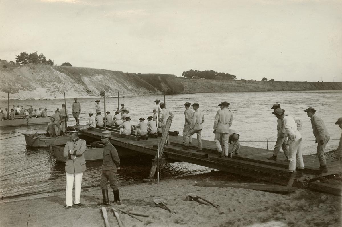 Elever från Krigsskolan Karlberg bygger pontonbro över vattendrag.