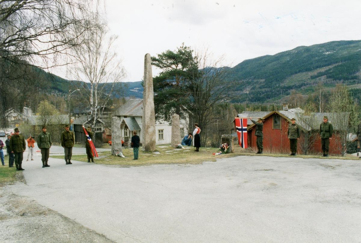 Gruppe,militær uniform,jakke,bukse og musikkuniform. Inger Bråten legger ned krans ved bautaen til bestefar sin Tor Bråten. Knut Breibrenna er nr. 2 frå høgre.