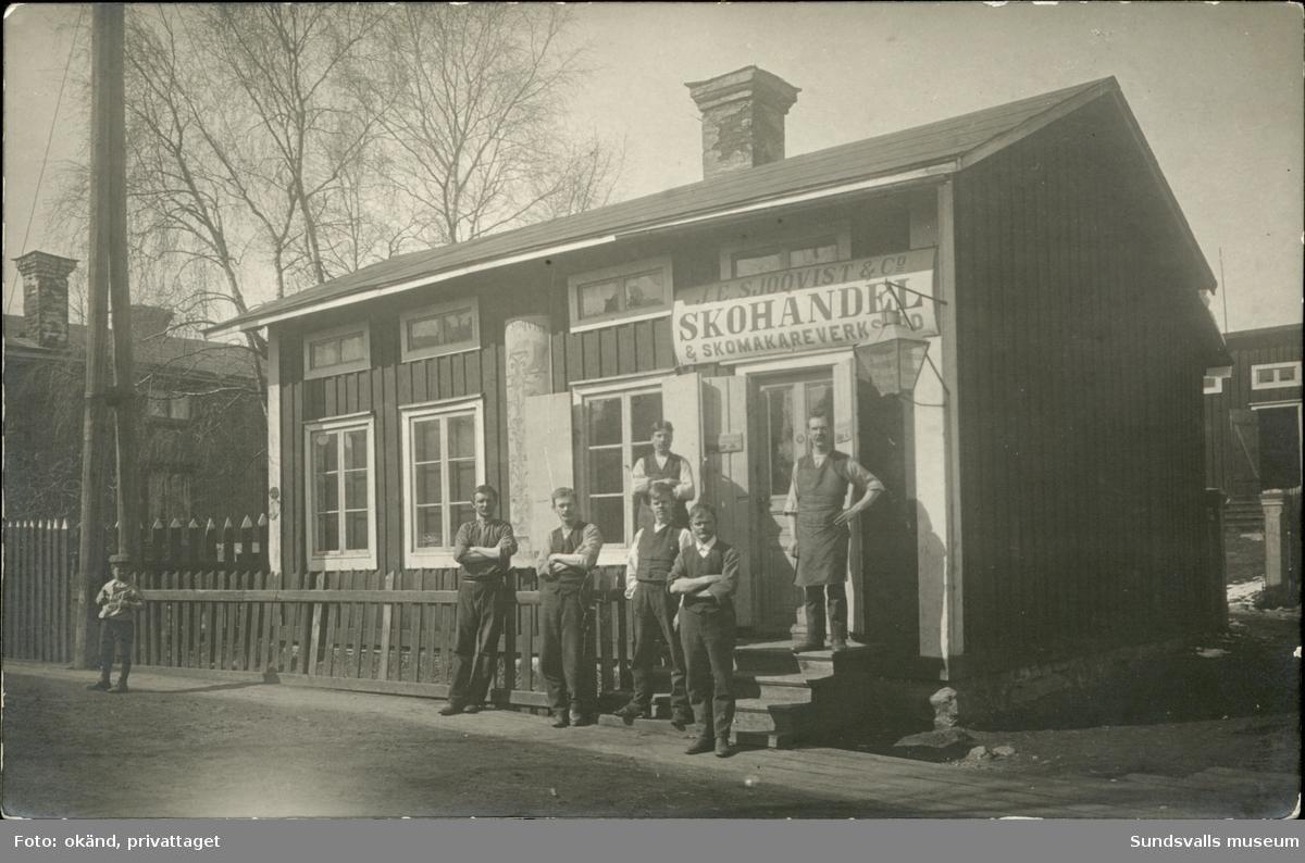 Vykort med motiv av en skohandel och skomakeri på Ortviksvägen i Skönsberg, med personalen uppställd utanför.