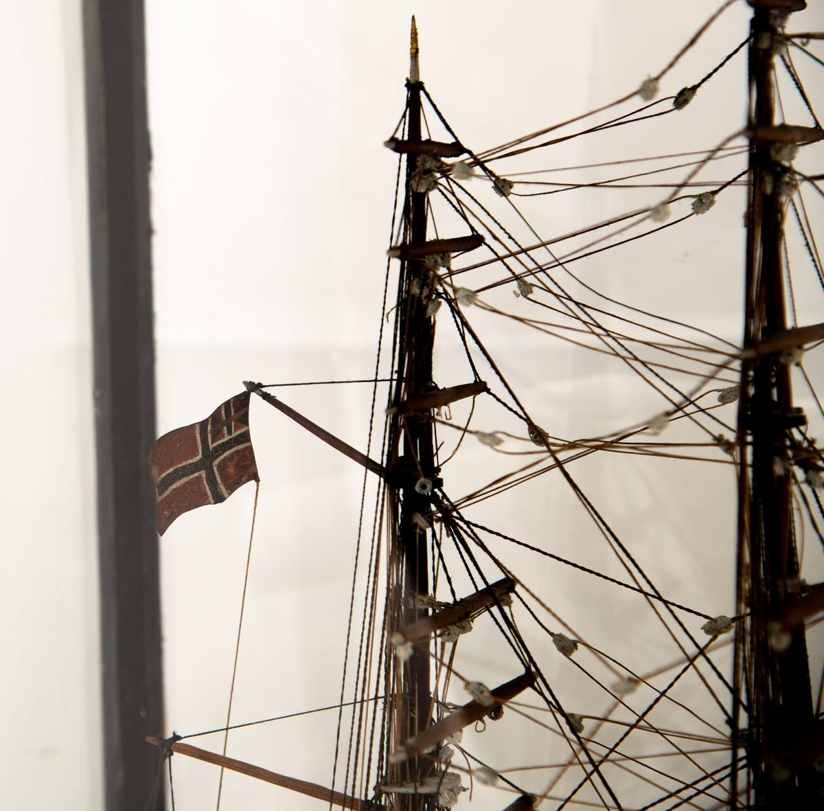 """Modell av fullrigger """"Skare"""".  (i glasskasse). Sortmalt  tre  med   forgylt  kjøl på mørkeblå ruglet bunn av  gips eller leire.  Kasse med glassvegger, sort ramme og  huntonittplate på toppen. Tremaster uten seil, unionsflagg akter, svensk-norsk. En livbåt ligger løs i bunnen,"""