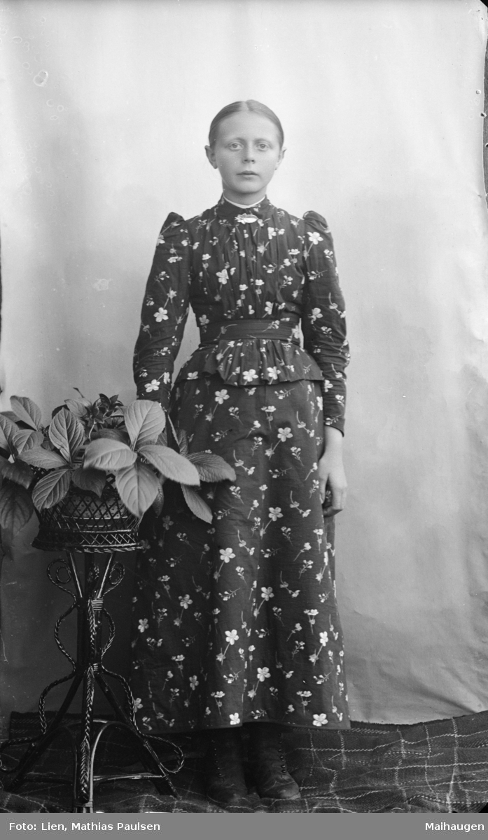 Kvinne som står ved siden av et rottingbord med blomster. Hun har glatt hår med midtskill, kledd i lang stakk og overdel med puffermer i blomstrett stoff