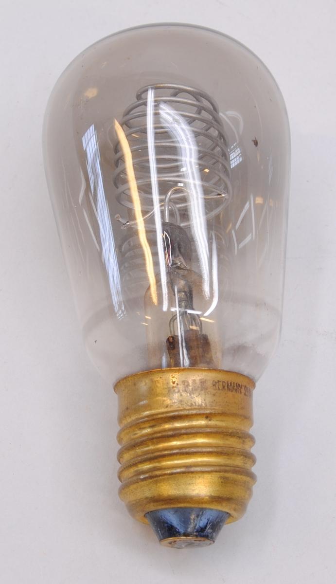 """Glödlampa, kallad glimlampa, med kupa av genomskinligt glas och sockel med bajonettfattning av mässing. På sockeln finns märkningen: """"OSRAM GERMANY 210-240V75.1710"""", tryckt i svart."""