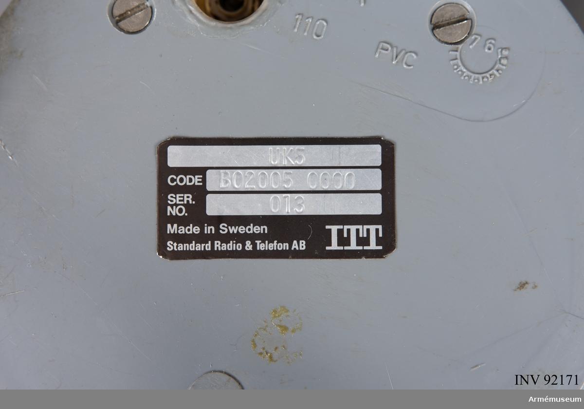 """Grön störsändare med blåvit fallskärm i fästband.   Bifogat dokument hittades tillsammans med föremålet:   """"Störsändare för att hindra radiotrafik. Någonstans söder Gävle 1977. Denna fallskärmsförsedda störsändare fälldes – tillsammans med åtskilliga andra – med helikopter över brigadstaben IB I4 under en brigadövning hösten 1977. Syftet var att förblinda radiotrafiken mellan staben och dess bataljoner. Det lyckades helt. Etern blev tyst och brigadchefen, överste Per-Arne Ringh tvingades tillgripa den gamla metoden med eskorterade stabsofficerarer till alla underlydande förband för att få fram sina order, vilket också lyckades, om än med viss fördröjning. Övningen följdes bl. a. av dåvarande arméchefen, generallöjtnant Nils Sköld. Överlämnad till Garnisonsmuséet av öv 1.gr P-A Ringh 1 februari 2008."""""""