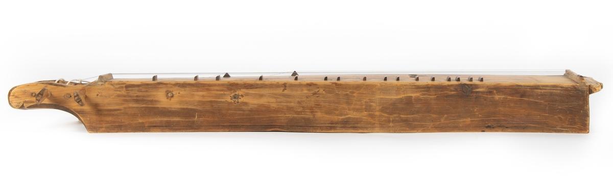 Langeleik av 1700-talstype, Nord-Valdres-typen, heilhola og utan botn. Seks stillarskruer (fem av dei laga av Olav Viken i 1984). Kasse (laga av Olav Viken i 1984), snert og arkivmateriale følgjer med.    Heildekkande stillarhus i eine enden, fin avsluttande skjørtekant i motsatt ende. Avfasing i over- og underkant av stillarhuset.   Tre skråstile profilliner (skore) på begge sider av stillarhuset. Reister etter skore profilliner på begge langsider, oppe og nede. Fint utskore hjarta, gjennombrote i loket, elles ingen dekor.