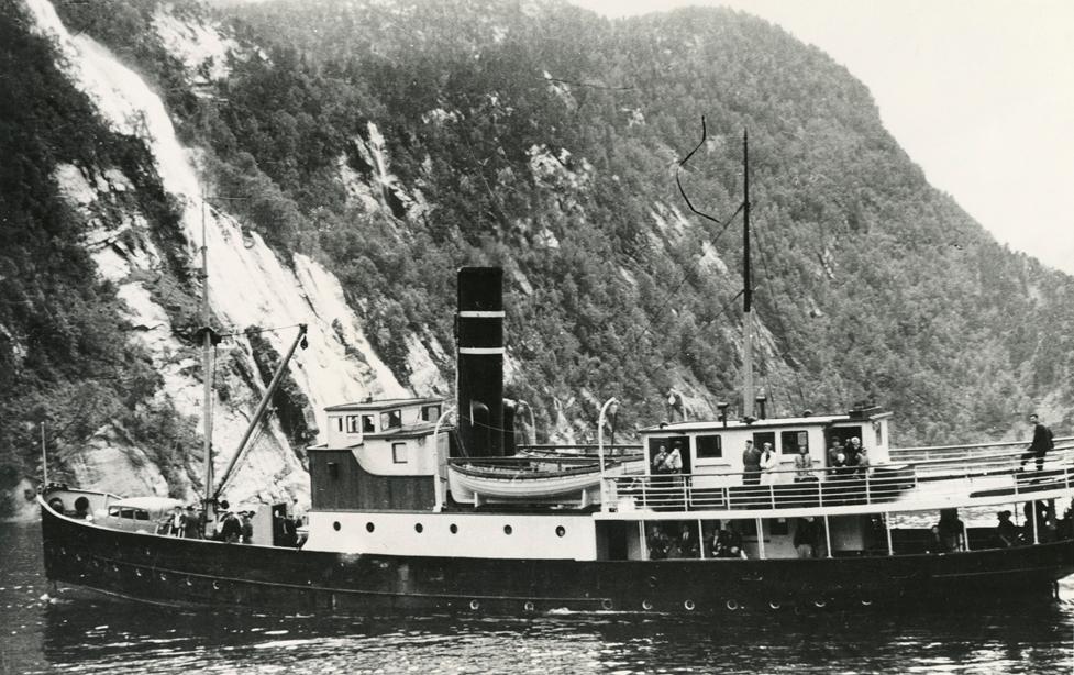 Motivet viser DS OSTER (bygget 1908) i kystlandskap.