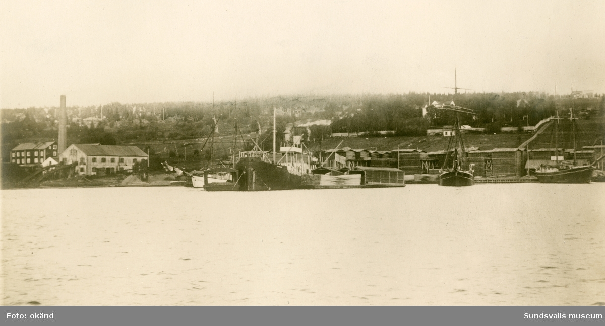 Sågverk och brädgård samt lastande fartyg vid Gustafshamns sågverk, Alnö. Fotografiet är taget från Johannedal.