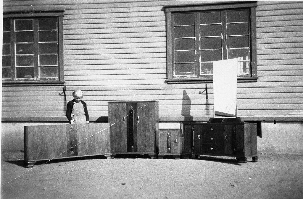 Maria Lura (1931 - ), dotter til Leonard Lura utanfor fabrikken deira. Gjenstandane er laga på fabrikken. Frå v. ei seng, toalettskap, nattbord og sjenk.