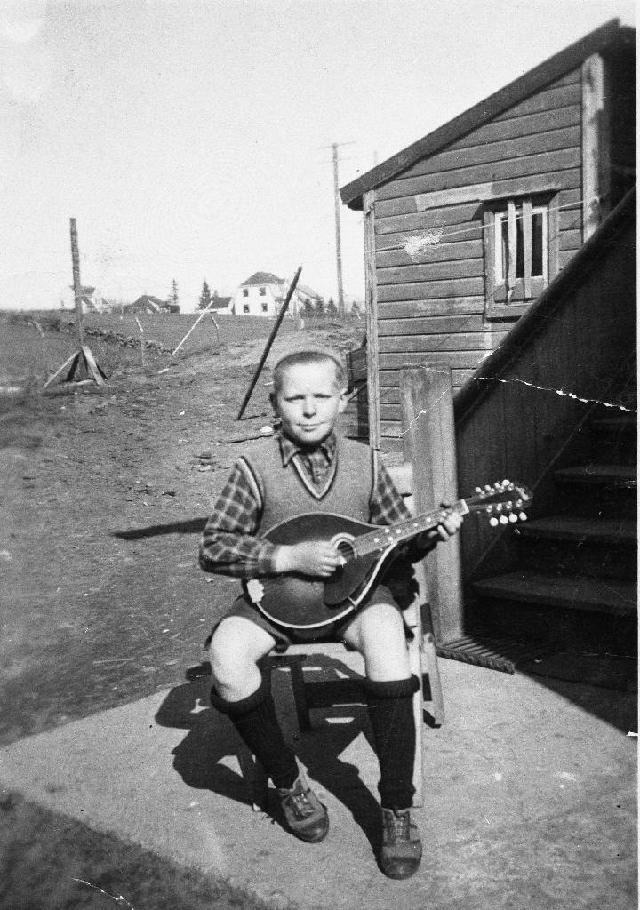 Johannes Stensland (1927 - ) med mandolin. Han sit i bakgarden på faren sin eigendom lengst vest i Storgata. Her er det nå parkering (1990). Johannes og faren John Juliusson Stensland (1896 - 1972) spela mandolin medan mora Elen Johanne f. Serigstad (1900 - 1976) song.