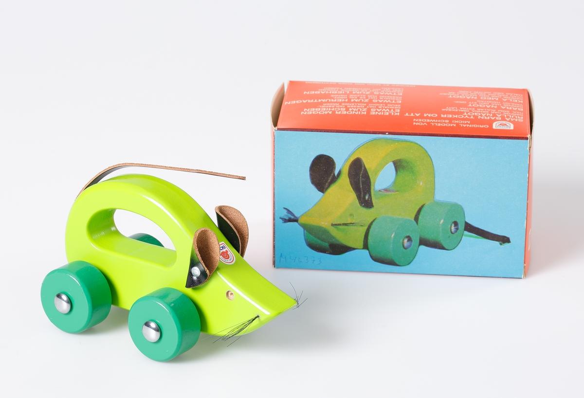 Grönlackerad mus, med ryggen utformad som ett handgrepp. Hjulen är lackerade i mörkare grön färg. Öronen och svansen är tillverkade av läderbitar. Morrhåren är gjorda av plast.  Design: Inger Westerberg.  Den är förpackad i en röd och blå pappkartong med bild och text på tyska, engelska och svenska.