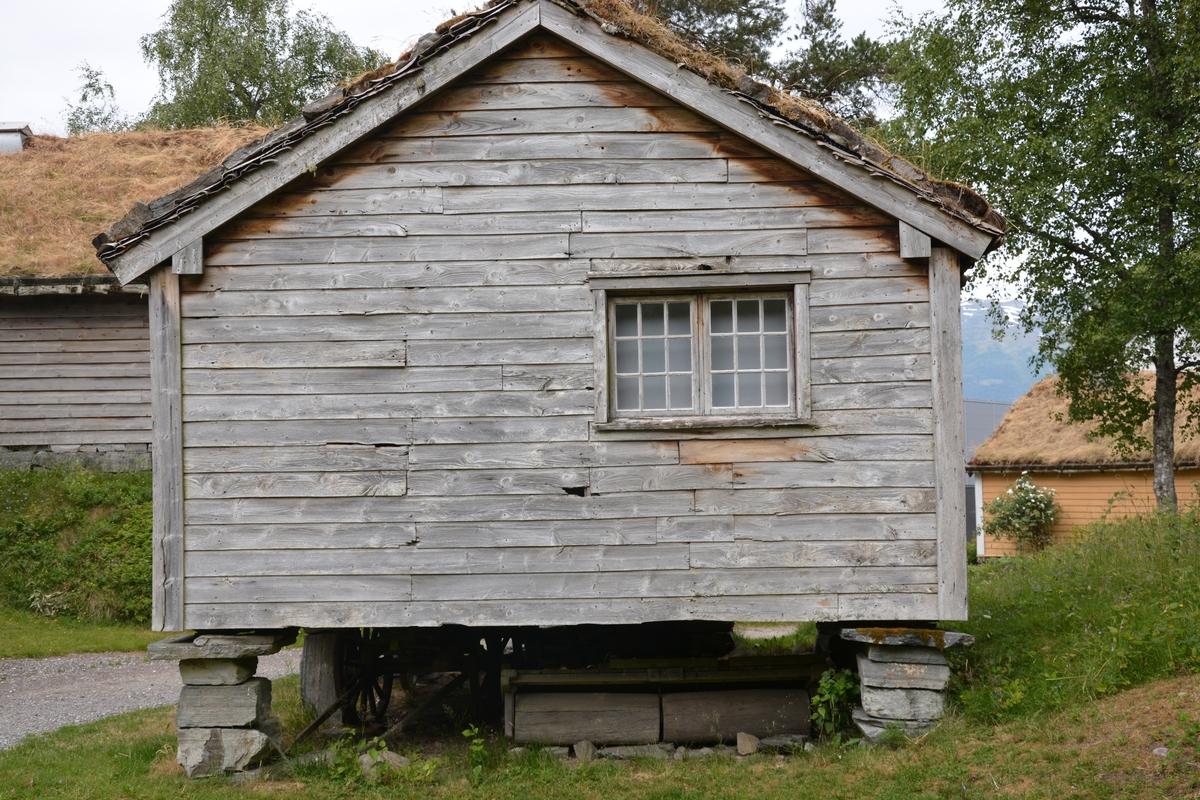 """Tømra bygning (1 rom) med bindingsverk i """"døra"""" (gangen) Utvendig supanel. Stabbar av stein. Torvtak. Vindu i gavlvegg. Hovudrommet har ei omlag kvadratisk golvflate. På høgre side er det fem kornbingar.  Dekormåla på innsida, limfargar, truleg 1600-tals. I venstre hjørne nærast døra er det det spor etter ei grue (Dette feltet er ikkje måla).   Døropninga har på kvar side ei bogeforma utviding (gjort for å få tønner ut?)  Døra har spor etter dekormåling.  I øvre kanten av døra står """"Herren din Gud bevare din Indgangog Udgang til eveig tid"""".  På øvste åken på døra står """"1603 IM"""" På andre sida av døra står """"Herren din Gud er en nidkjær Gud"""". På sørveggen innanfor kornbingane står """"Margreth"""". Spor i veggane viser ombyggningar, utskifting av bord og felt utan måling. I det umåla feltet i det eine hjørnet er det spor etter ei grue.   Tak og gavl er det måla blomster i raudt og svart mot kvit botn. På veggane er det måla søyler og boger med bladkransar inne i bogane. Der er også ei frise/band med grøne trekruner mot kvit botn, fulgar og dyr. Dekormålinga kan delast inn i tre grupper etter stil/motiv:  - Klassisistisk arkitekturmotiv, søyler med boge over - Frodig blometerbarokk med ranker og kransar - Tre, dyr og fuglar"""