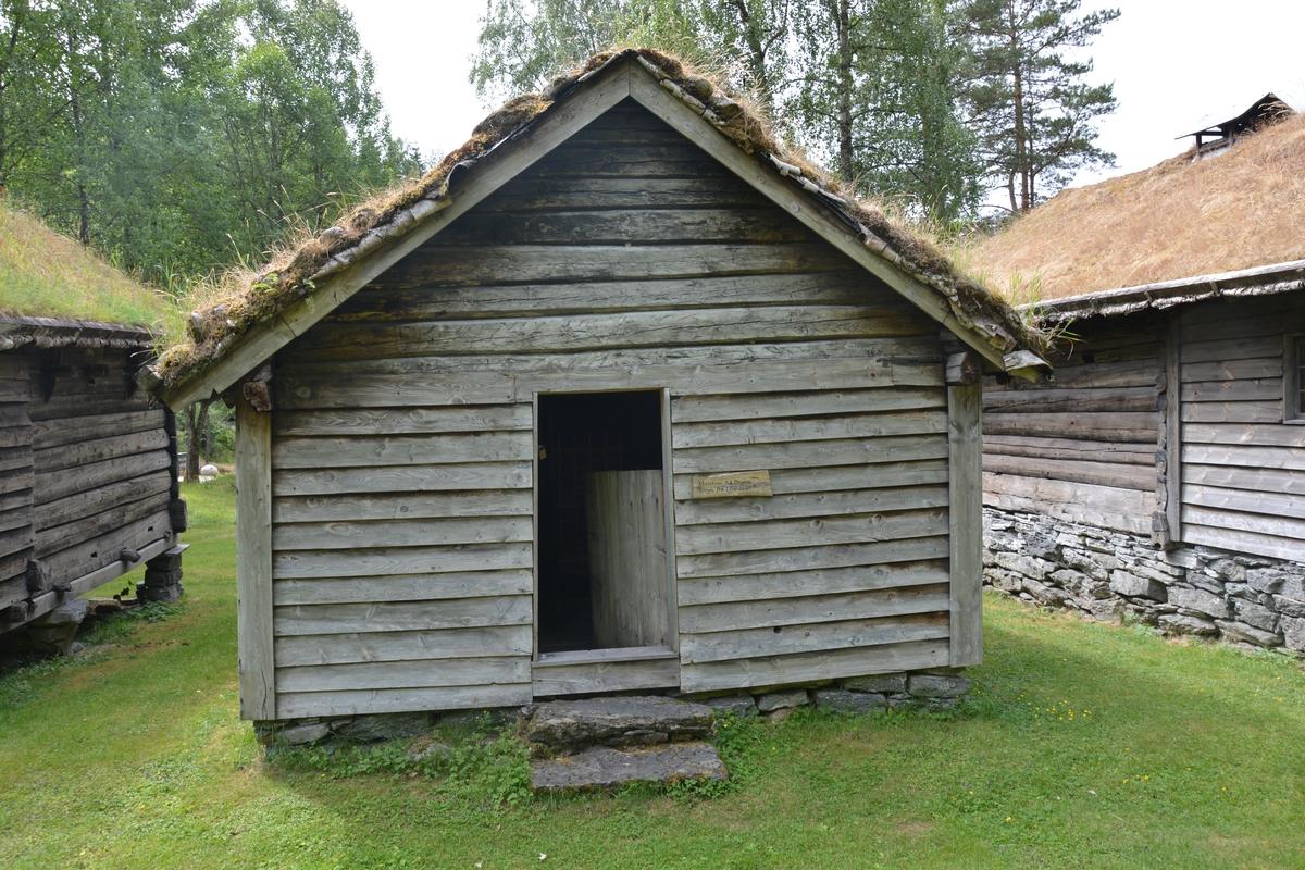 """Tømra bygning med 2 rom, stove og forstove. Forstova / """"døra"""" bygd i reisverk med supanel. Tørrmur. Torvtak. Grue i ytterste rom (""""døra""""), bileggeromn i innerste. Bileggaromenen er sekundær."""