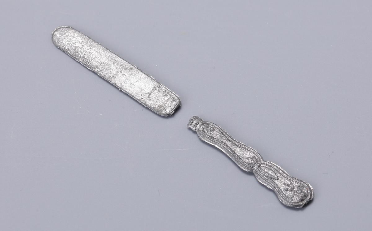 M 13464:a-b. Kniv och gaffel, för dockorna. I mjuk metall med lite ornament på skaften.