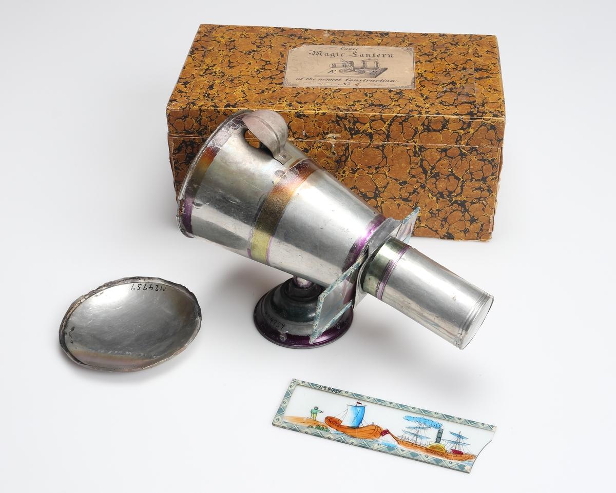 """Laterna magica av bleckplåt. Blank med ränder i gult, grönt och lila. Apparaten är konisk till utförandet och vilar liggande på en rund fotplatta, och är försedd med en glaslins som förstorar upp bilderna på väggen.Ljuskällan bestpr av 1 st. stearin- eller vaxljus. Apparaten förvaras i en trälåda klädd med papper i gult och svart mönster. Lådan innehåller även 13 st. bildserier att användas i apparaten. Bildserierna är uppfästade på glasplåtar.  Apparaten är märkt: """"Conic Magic Lantern of the newest Construction, No 4""""."""