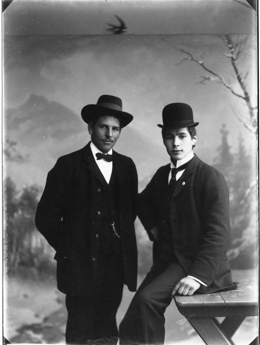 Gruppbild med två unga män i kostym med fluga respektive kravatt och hatt på huvudet. Det är Anton Johansson till vänster och Carl Ture Roman till höger som halvsitter på ett bord. Ateljébild med vinterlandskap som bakgrund.