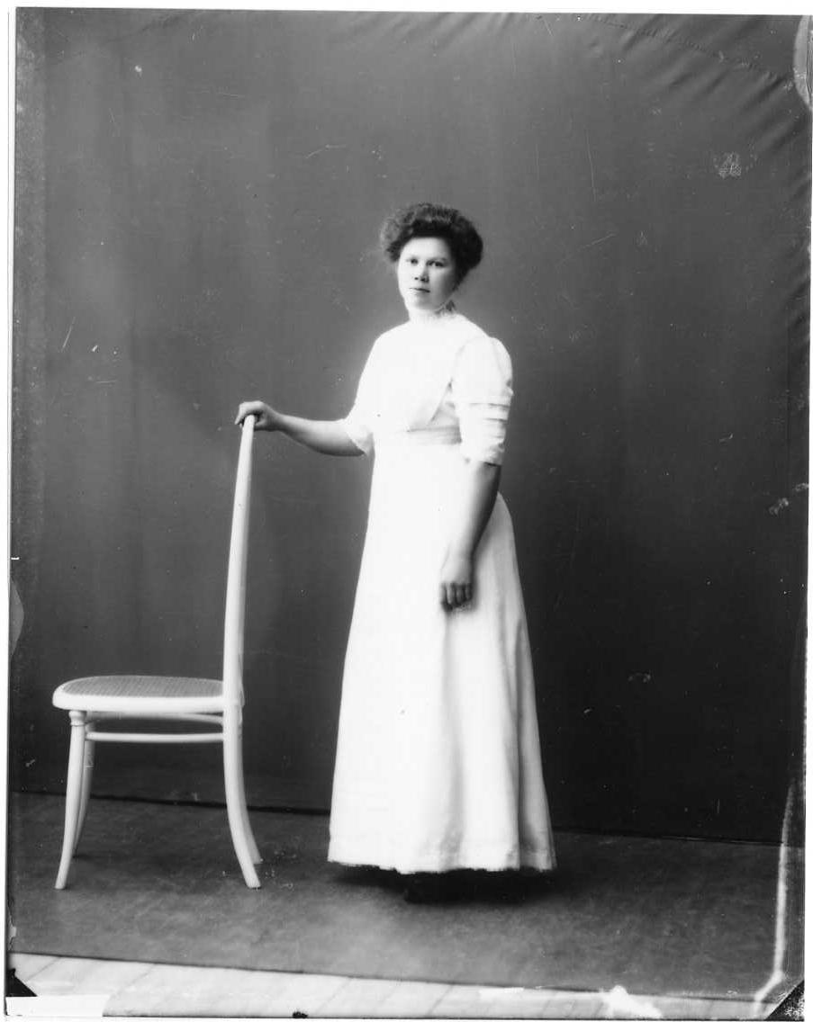 Porträtt av Rut Andersson från Örserum. Hon står i en fotsid ljus klänning med höger hand vilande på en stolsrygg.
