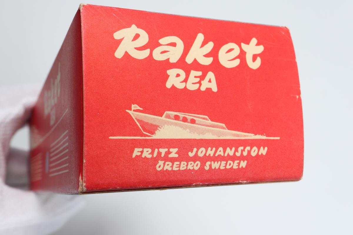 """Båt (leksak) tillverkad av lackerad plåt i färgerna blått, rött och vitt. Framdrives genom upphettning av ett membran, eldas med s.k. """"Metatableter"""". Båten går framåt i vattnet av den s.k. """"Reaprincipen"""".  Förvaras i originalförpackning."""