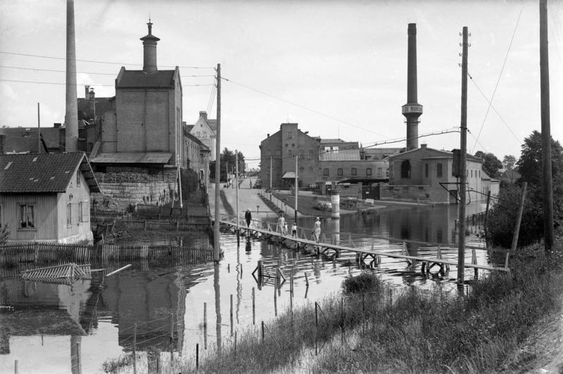 Svart-hvitt fotografi som viser en vannfylt gate med provisorisk bro over, et lite plankehus til venstre og to store murbygninger; Hamar bryggeri og melkefabrikken med en høy, rund mursteinspipe. (Foto/Photo)