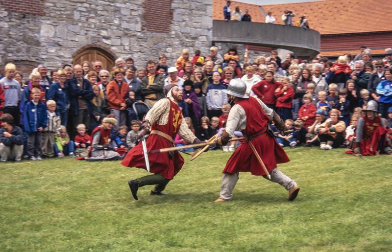 To riddere i rustning og med røde overkapper utkjemper blankvåpenkamp foran Storhamarlåven. Mellom ridderne og låven er det en stor menneskemengde som ser på kampen.